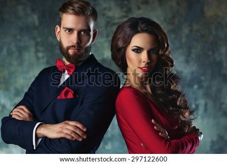 Young elegant couple in evening dress portrait. Standing shoulder to shoulder. - stock photo