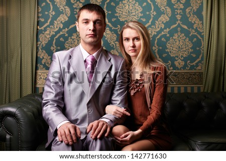 Young elegant couple looking at camera indoors