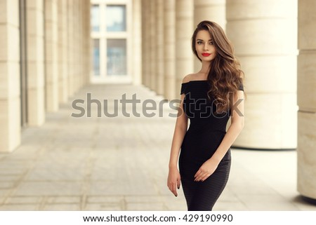 Young elegant girl posing at city street. Pretty beautiful business woman in elegant black dress against city background.
