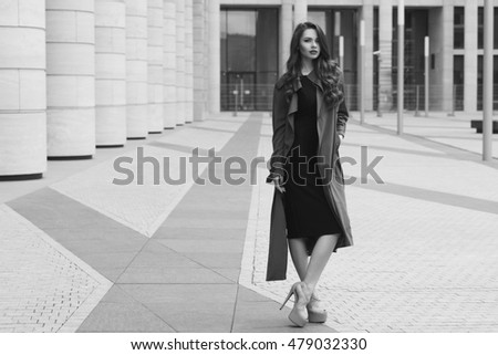 Young elegant girl posing at city street. Pretty beautiful business woman in elegant black dress and gray coat against city background. Full length horizontal portrait.