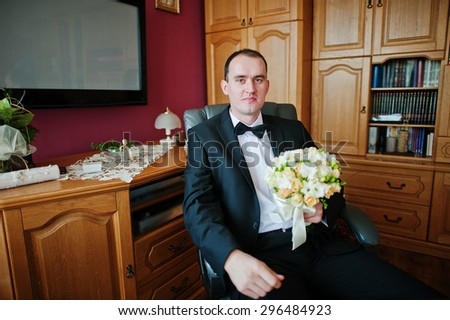 Young elegant groom with bouquet