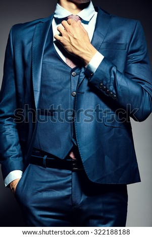 Young  elegant handsome  businessman male model in a suit tying the necktie - stock photo