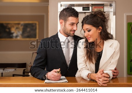Young elegant happy couple at hotel reception with key room. - stock photo
