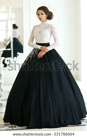Young elegant lady in black and white evening dress with fluffy skirt posing and standing in white interior - stock photo