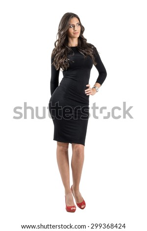 Young elegant lady in black dress looking away with hand on her hip. Full body length portrait isolated over white studio background.  - stock photo