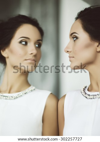 young elegant lady in front of mirror, soft focus