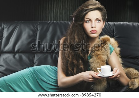 young elegant lady laying down on sofa keeping and drinking from a little cup of coffee. wearing green dress. she is lying on the sofa, looks at the left and takes the cup with both hands. - stock photo