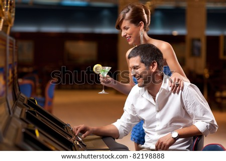 young elegant lady standing, boyfriend playing slot machine