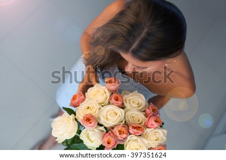 Young elegant lady with beautiful bouquet of roses. (focus on nose) - stock photo