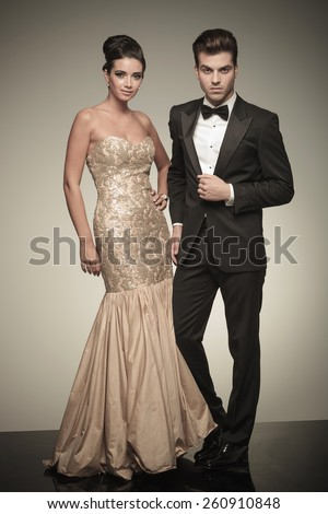 Young elegant man and woman posing next to each other on grey studio background. - stock photo