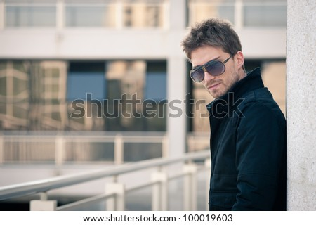 Young elegant man portrait with glasses with building background.