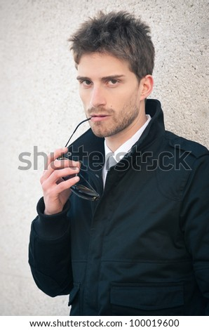 Young elegant man portrait with sunglasses against a wall. - stock photo