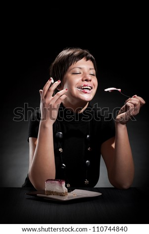 Young elegant woman eating a chocolate cake and making a mess