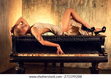 Young elegant woman in dress lying on piano in retro style interior. - stock photo