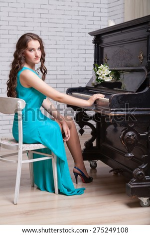 Young elegant woman in dress sitting near piano.  - stock photo
