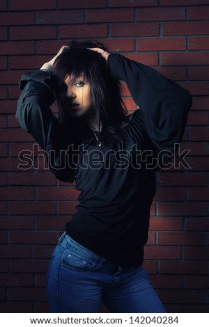 Young elegant woman in front of brick wall backround