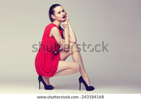 young elegant woman in red dress and black shoes, fashion studio shot  - stock photo