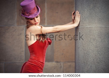 young elegant woman in red dress and cylinder  leaning against column - stock photo