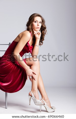 young elegant woman in red dress sit on chair, studio shot - stock photo