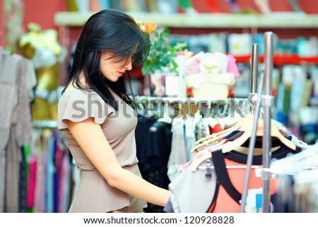 young elegant woman shopping in clothes store