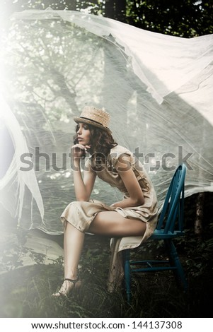 young elegant woman sit in summer garden with veil  flutter behind her - stock photo