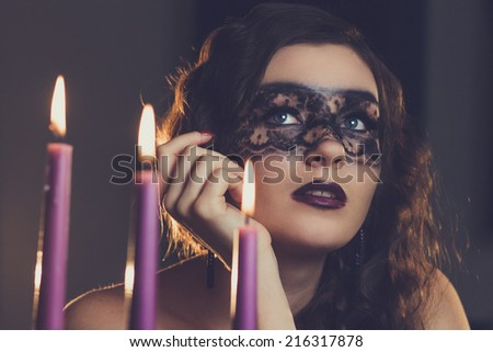 young elegant woman sitting near candles with make-up mask - stock photo