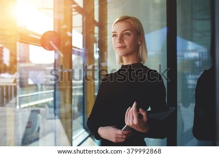 Young elegant woman thinking something while standing with touch pad near office window outside, female employer holding digital tablet while looking forward to meeting with international partners - stock photo