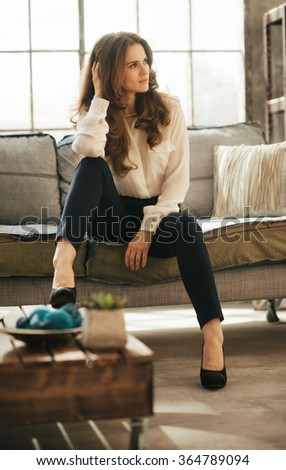 Young elegant woman with brown hairs sitting on couch in loft apartment