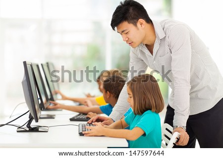 young elementary school teacher teaching students in computer room - stock photo