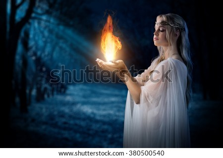 Young elven girl holding fire in palms at night forest - stock photo