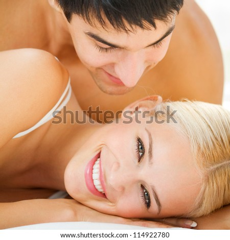 Young embracing cheerful attractive couple on bed - stock photo
