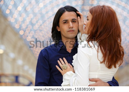 Young embracing couple - dark-haired man and red-haired woman