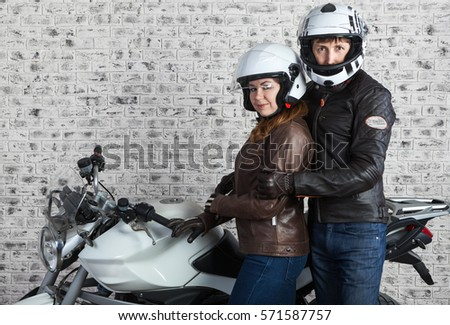 Young embracing couple in a motorcycle outfit standing together near the motorbike in the garage