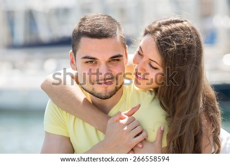 Young embracing couple taking sunbaths on the pier at summer day