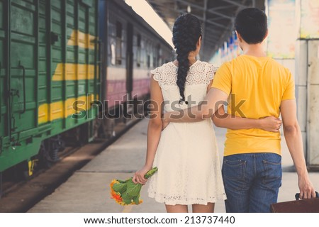 Young embracing couple walking along the platform, rear view - stock photo