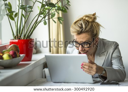 Young emotional business woman looking at the laptop monitor with surprise and joy. - stock photo
