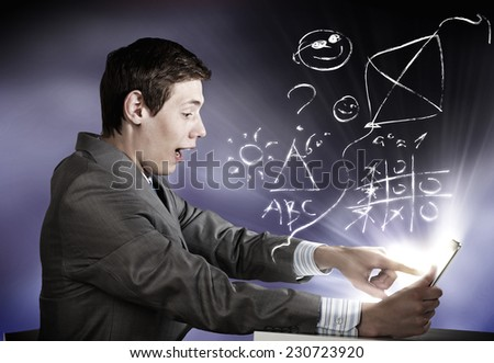 Young emotional businessman looking shocked in tablet pc