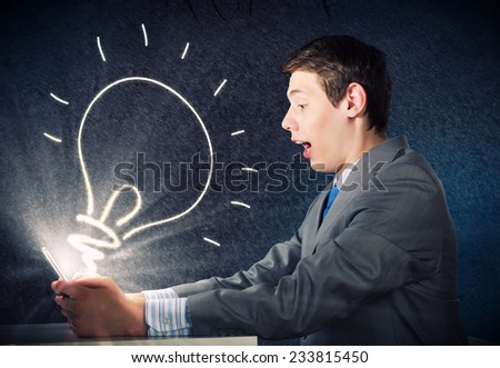 Young emotional businessman looking shocked in tablet pc - stock photo