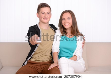 Young emotional couple watching TV, sitting on the sofa at home - stock photo