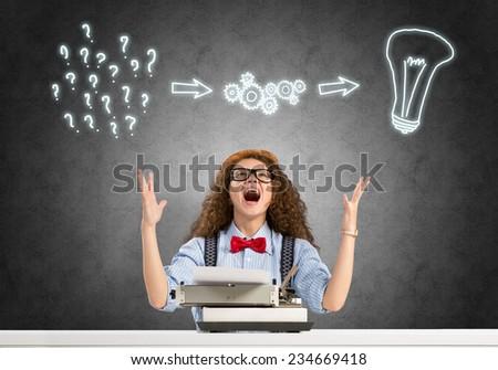 Young emotional girl writer using typing machine - stock photo