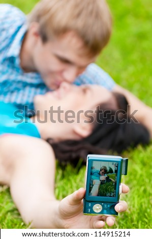Young emotional happy teenage couple taking picture on grass in city park - stock photo