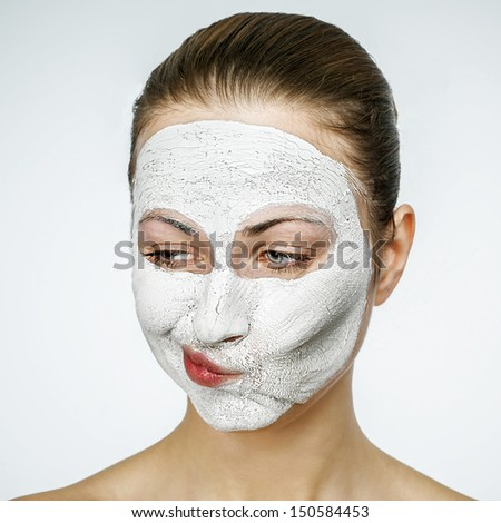Young emotional woman with facial mask screaming