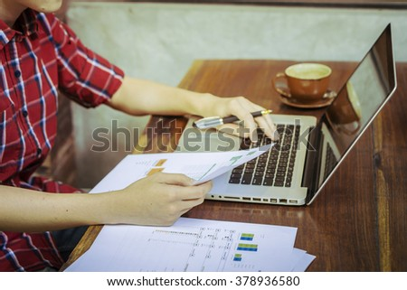 young employee analyzing financial data in office,businessman sitting in front of net book in office,analyzing financial chart,writing business plan ,working on his laptop in coffee shop,vintage tone - stock photo