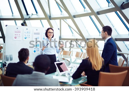 Young employee giving a presentation to business people - stock photo