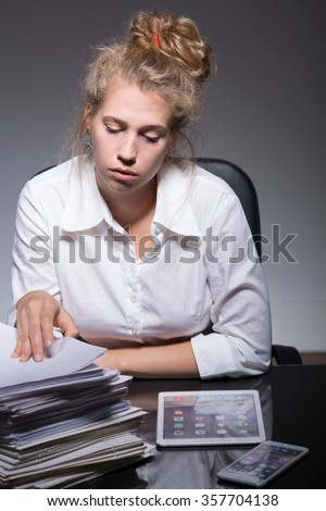 Young employee has problem with managing paperwork - stock photo