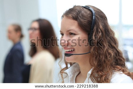 Young employee working with a headset and accompanied by her team