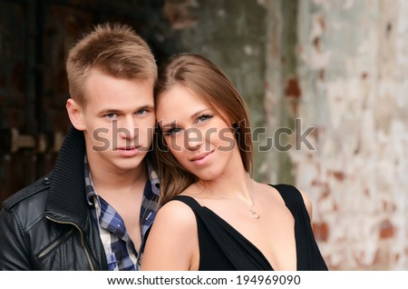 Young enamoured pair at a brick wall - stock photo