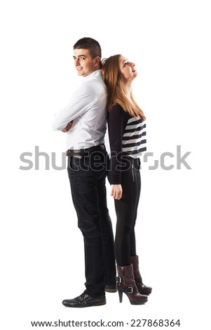 Young energetic couple standing back to back - isolated on white.