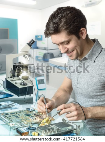 Young energetic male tech or engineer repairs electronic equipment in research facility. Shallow DOF, focus on the face and left hand of the worker. - stock photo