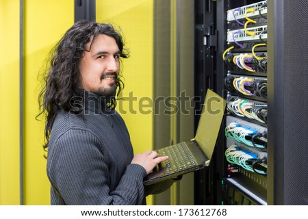 young engeneer professional technician with modern laptop in computer server room - stock photo